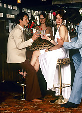 Seventies girl gets a free cocktail in a bar from two guys
