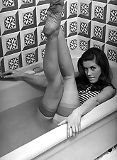 Sexy chick in retro lingerie gets into the bathtub in order to pose right there before the camera